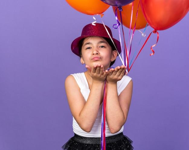 Satisfeita jovem caucasiana com chapéu de festa violeta segurando balões de hélio e mandando beijo com as mãos isoladas na parede roxa com espaço de cópia