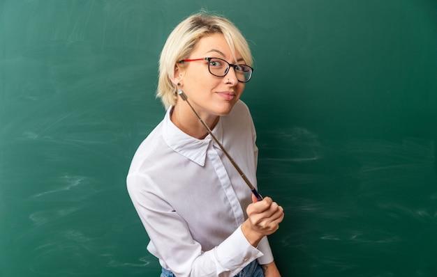 Satisfeita jovem professora loira usando óculos na sala de aula em pé em vista de perfil na frente do quadro-negro, olhando e apontando para a frente com um ponteiro com espaço de cópia