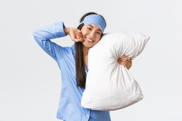 Satisfeita linda garota asiática de pijama azul e máscara de dormir, deitada na cama e abraçando o travesseiro, sorrindo de satisfação enquanto alongamento e se sentindo bem depois de uma noite de sono, parede branca.