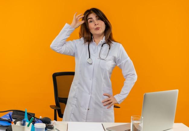 Satisfeita médica de meia-idade vestindo túnica médica com estetoscópio sentada na mesa de trabalho no laptop com ferramentas médicas colocando os dedos na cabeça na parede laranja isolada com espaço de cópia