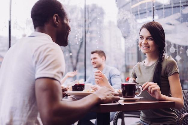 Satisfeita mulher irresistível segurando o garfo enquanto sorri e olha para o homem