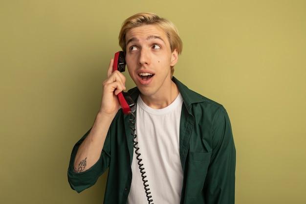 Satisfeito ao olhar para o lado, jovem loiro de camiseta verde fala ao telefone