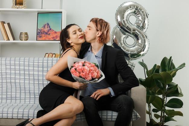 Satisfeito beijando um ao outro jovem casal no dia da mulher feliz, garota segurando buquê sentada no sofá na sala de estar