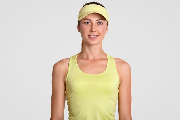 Satisfeito bonito jovem tenista ativo, vestido com boné amarelo e camiseta, tem uma pele saudável, posa contra uma parede branca, vem do tribunal, feliz em ganhar o jogo. pessoas e fitness