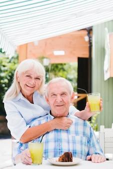 Satisfeito casal sênior abraçando no café no terraço, apreciando a bebida refrescante e bolo