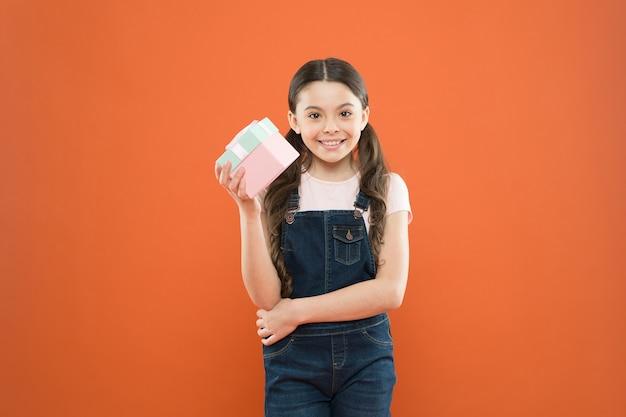 Satisfeito com as compras. criança pequena segurando uma caixa de presente em fundo laranja. menina depois de comprar um presente. gracinha, gostando de fazer compras. viciado em compras com presente embrulhado em caixa.