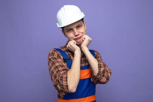 Satisfeito com as mãos ao redor do rosto, jovem construtor do sexo masculino vestindo uniforme