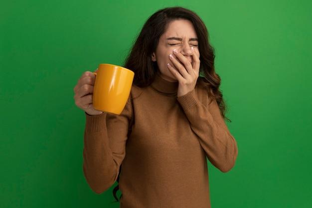 Satisfeito com os olhos fechados, a bela jovem segurando uma xícara de chá e a boca coberta com a mão isolada na parede verde