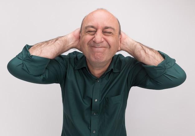 Satisfeito com os olhos fechados, homem de meia-idade vestindo camiseta verde e colocando as mãos atrás da cabeça, isolado na parede branca