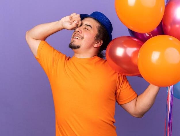 Satisfeito com os olhos fechados, jovem usando chapéu de festa segurando balões, limpando os olhos com a mão isolada na parede roxa