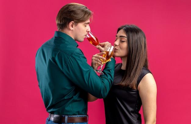 Satisfeito com os olhos fechados, um jovem casal no dia dos namorados bebe champanhe isolado em um fundo rosa