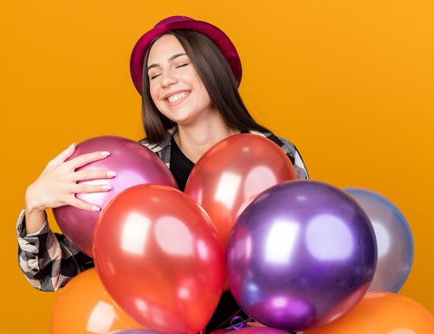 Satisfeito com os olhos fechados, uma jovem mulher bonita usando um chapéu de festa em pé atrás de balões isolados na parede laranja