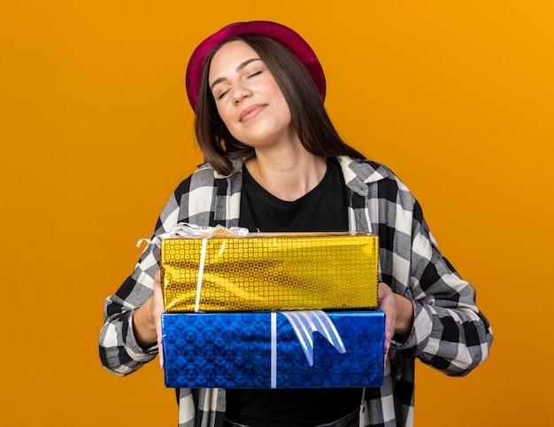 Satisfeito com os olhos fechados, uma jovem mulher bonita usando um chapéu de festa segurando caixas de presente isoladas na parede laranja