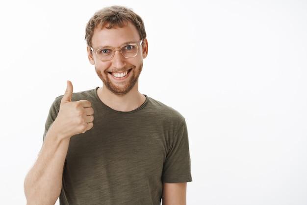 Satisfeito e satisfeito, animado, homem europeu engraçado com cerdas nos óculos e camiseta verde casual mostrando os polegares para cima e sorrindo alegremente aprovando a boa ideia