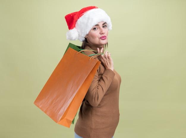 Satisfeito, em pé na vista de perfil, jovem linda com chapéu de natal segurando uma sacola de presente no ombro isolada em fundo verde oliva