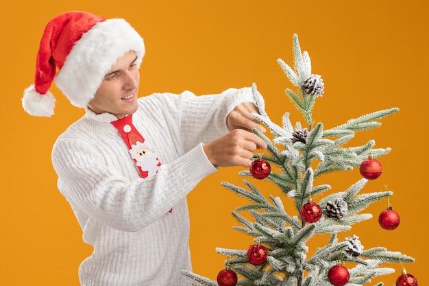 Satisfeito jovem bonito usando chapéu de natal e gravata de papai noel em pé perto da árvore de natal decorando-o com enfeites de bola de natal isolados na parede laranja