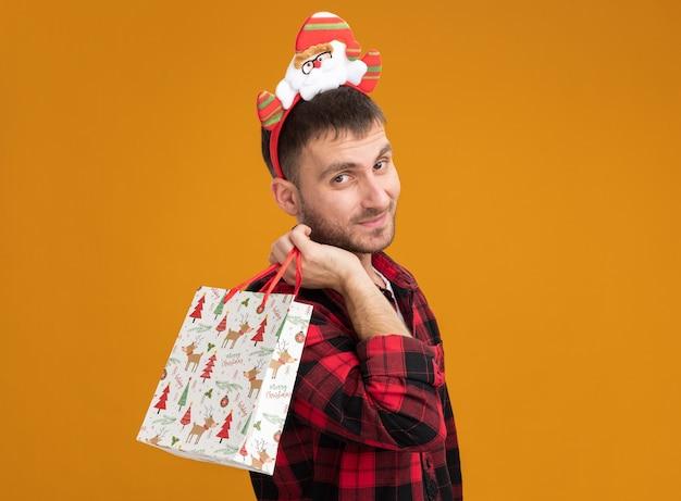 Satisfeito jovem homem caucasiano com fita de papai noel em pé na vista de perfil, segurando uma sacola de presente de natal no ombro, parecendo isolado na parede laranja com espaço de cópia