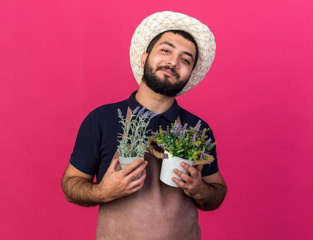 Satisfeito jovem jardineiro caucasiano com chapéu de jardinagem segurando vasos de flores isolados na parede rosa com espaço de cópia