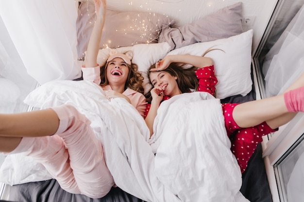 Satisfeito o modelo feminino deitado sob o cobertor branco e rindo. foto interna de duas meninas alegres, passando a manhã de fim de semana na cama.