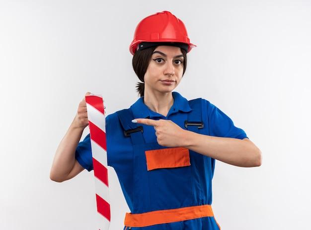 Satisfeito, olhando para a câmera, a jovem construtora de uniforme segurando e apontando para a fita adesiva