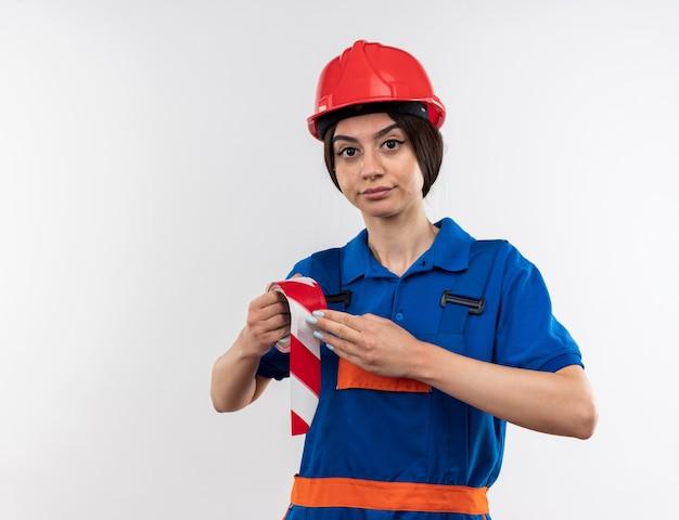 Satisfeito, olhando para a câmera, jovem construtor de uniforme segurando fita adesiva