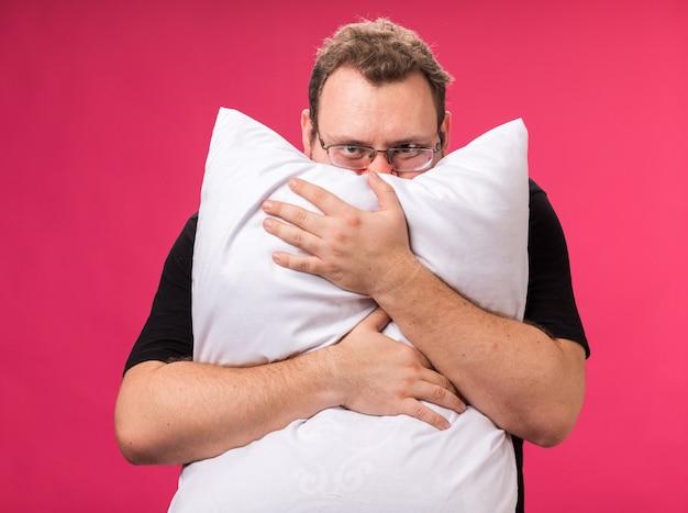 Satisfeito, olhando para a câmera, um homem doente de meia-idade, um travesseiro abraçado