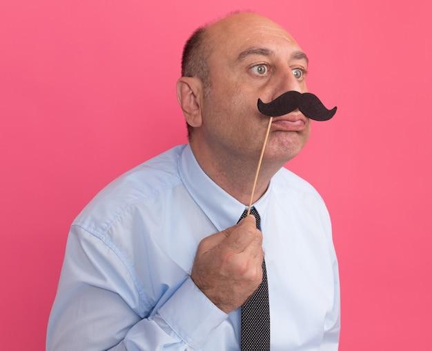 Satisfeito, olhando para o lado de um homem de meia-idade vestindo uma camiseta branca com gravata segurando um bigode falso em um palito isolado na parede rosa