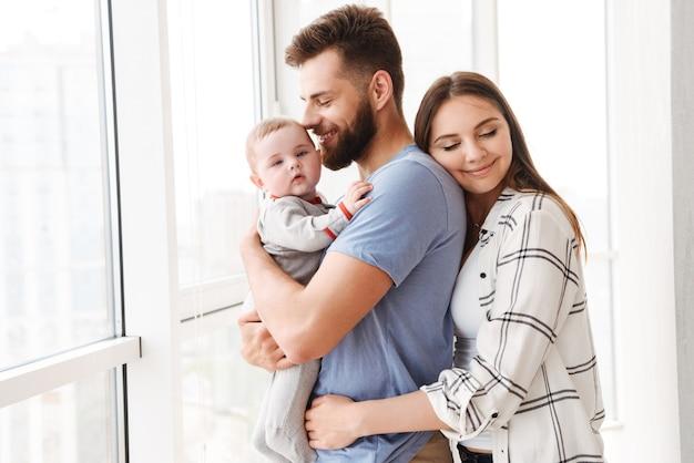 Satisfeito os pais do casal amoroso, segurando nas mãos seu filho pequeno.