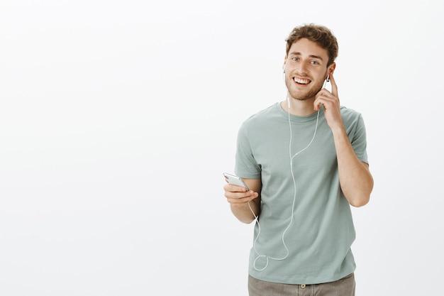 Satisfeito satisfeito modelo masculino caucasiano com cerdas, segurando o smartphone e tocando o fone de ouvido enquanto ouve música e desfruta do som dos fones