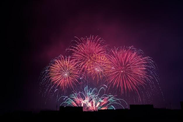 Saudação bonita colorida dos fogos-de-artifício contra o céu nocturno escuro.