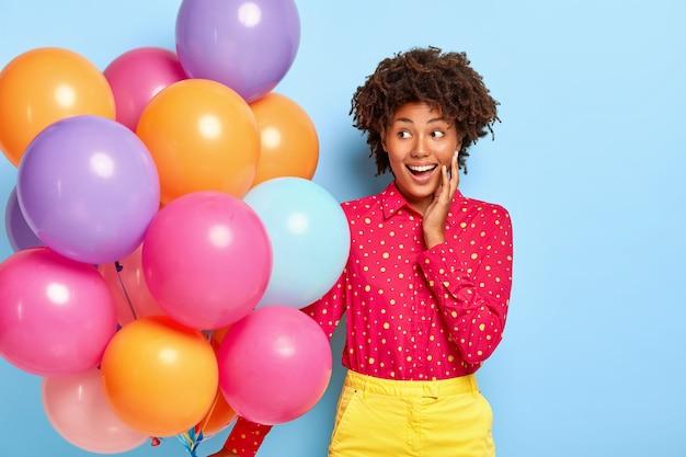 Saudação de aniversário. senhora positiva com penteado afro, olhando para o lado