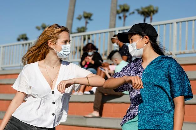 Saudação de cotovelo, adolescentes ao ar livre no novo normal
