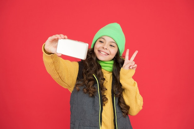 Saudação de feliz natal. parabéns de ano novo. menina adolescente feliz fazendo selfie com smartphone. compras online de inverno de natal. moda da estação fria. criança em roupas quentes. ligar para a família nas férias.