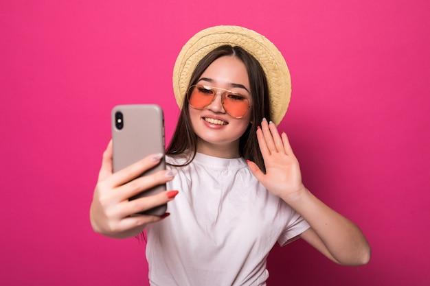 Saudação de mulher asiática no telefone inteligente, na parede rosa