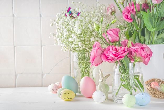 Saudação de páscoa feliz, fundo de cartão de convite. composição de flores de primavera com ovos de páscoa coloridos e flores de primavera na mesa de madeira azul, com espaço de cópia para o texto. camada plana, vista superior.