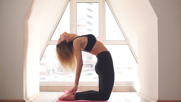 Saudação feminina jovem atraente yoga professor no início da prática de ioga