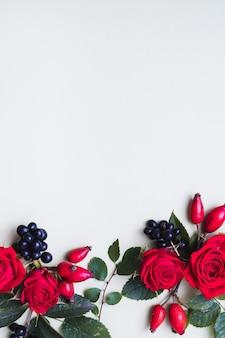 Saudação floral vermelho e preto caem bagas, folhas verdes e rosas em branco