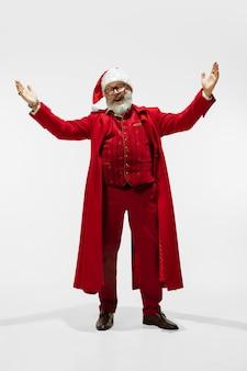 Saudação, homem. moderno e elegante papai noel em elegante terno vermelho, isolado no fundo branco. parece uma estrela do rock. reveillon e natal, comemoração, feriados, clima de inverno, moda.
