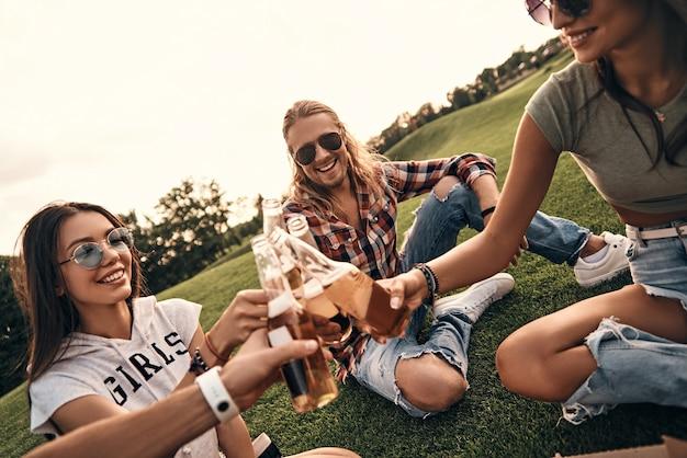 Saudações à amizade! grupo de jovens sorridentes em trajes casuais brindando com garrafas de cerveja enquanto fazem um piquenique ao ar livre