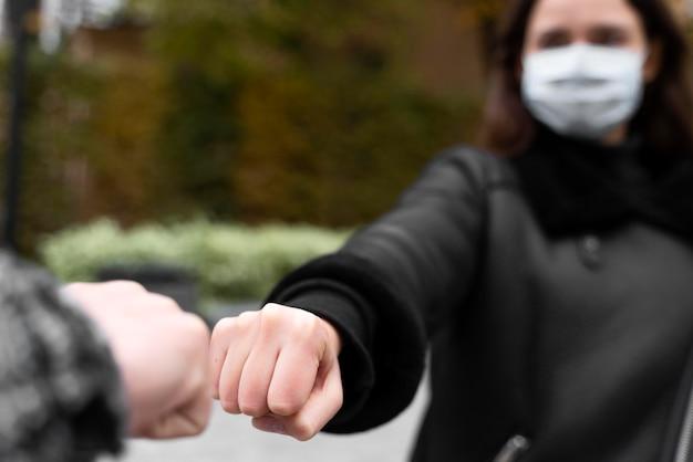 Saudações alternativas quase tocando punhos em mulher turva
