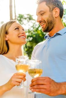 Saudações ao amor! vista de baixo ângulo de um jovem casal apaixonado, segurando copos com vinho branco e olhando um para o outro com um sorriso, enquanto estão juntos ao ar livre