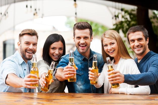 Saudações aos amigos! grupo de jovens felizes se unindo e estendendo garrafas com cerveja enquanto ficam do lado de fora