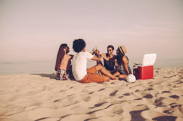 Saudações aos amigos! jovens alegres passando bons momentos juntos enquanto estão sentados na praia bebendo cerveja