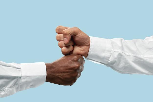 Saudações de amigos assinam ou discordam. competição de duas mãos masculinas na queda de braço isolada sobre fundo azul.