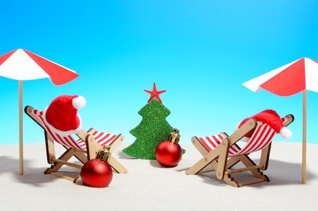 Saudações de natal sazonais de uma praia tropical com duas espreguiçadeiras, chapéus de papai noel, bugigangas e guarda-chuvas em vermelho e branco em frente a uma árvore de natal