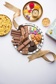 Saudações do festival raksha bandhan: rakhi conceitual feito com um prato cheio de chocolates e biscoitos com banda extravagante e pooja thali. foco seletivo