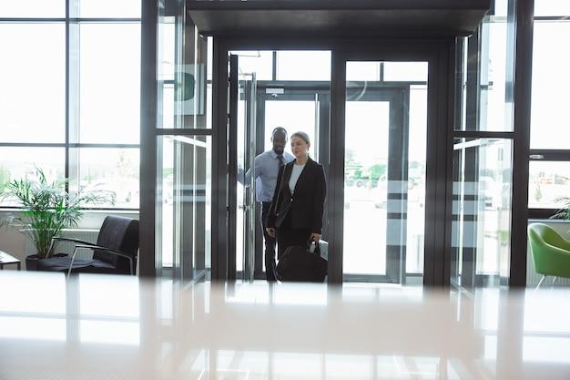 Saudações. encontro de jovens parceiros de negócios após chegada ao ponto final da viagem de negócios. homem e mulher caminhando contra o fundo da parede de vidro de um edifício moderno. conceito de negócios, finanças, anúncio.