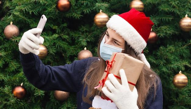 Saudações online de natal. feche o retrato de uma mulher com um chapéu de papai noel e uma máscara médica com emoção. no contexto de uma árvore de natal. pandemia do coronavírus