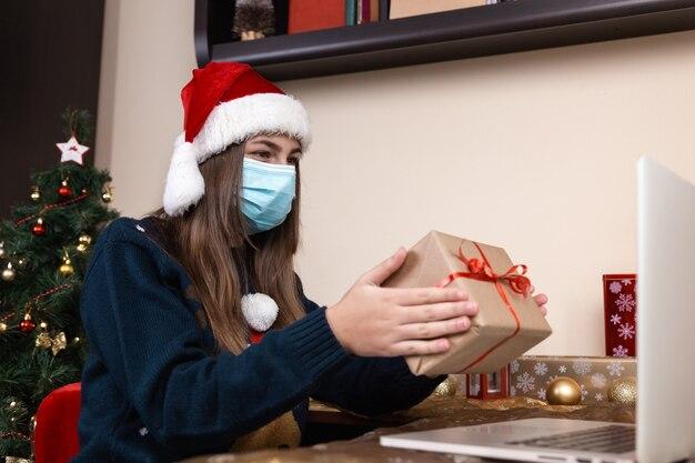 Saudações online de natal. garota com chapéu de papai noel em palestras de máscara médica dá um presente usando o laptop para pais e amigos de videochamada. o quarto está decorado de forma festiva. natal durante o coronavírus.