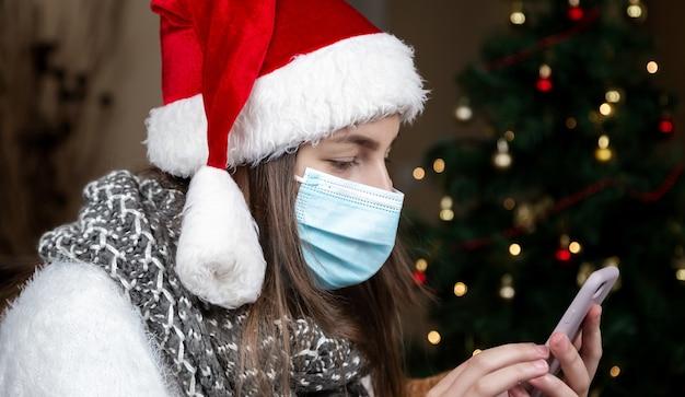 Saudações online de natal. uma jovem com um chapéu de papai noel e uma máscara médica fala usando o smartphone para pais e amigos de videochamada. natal durante o coronavírus